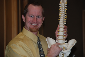 Dr. Matt Kiewall in his Fort Collins chiropractic office holding a model of the human spine